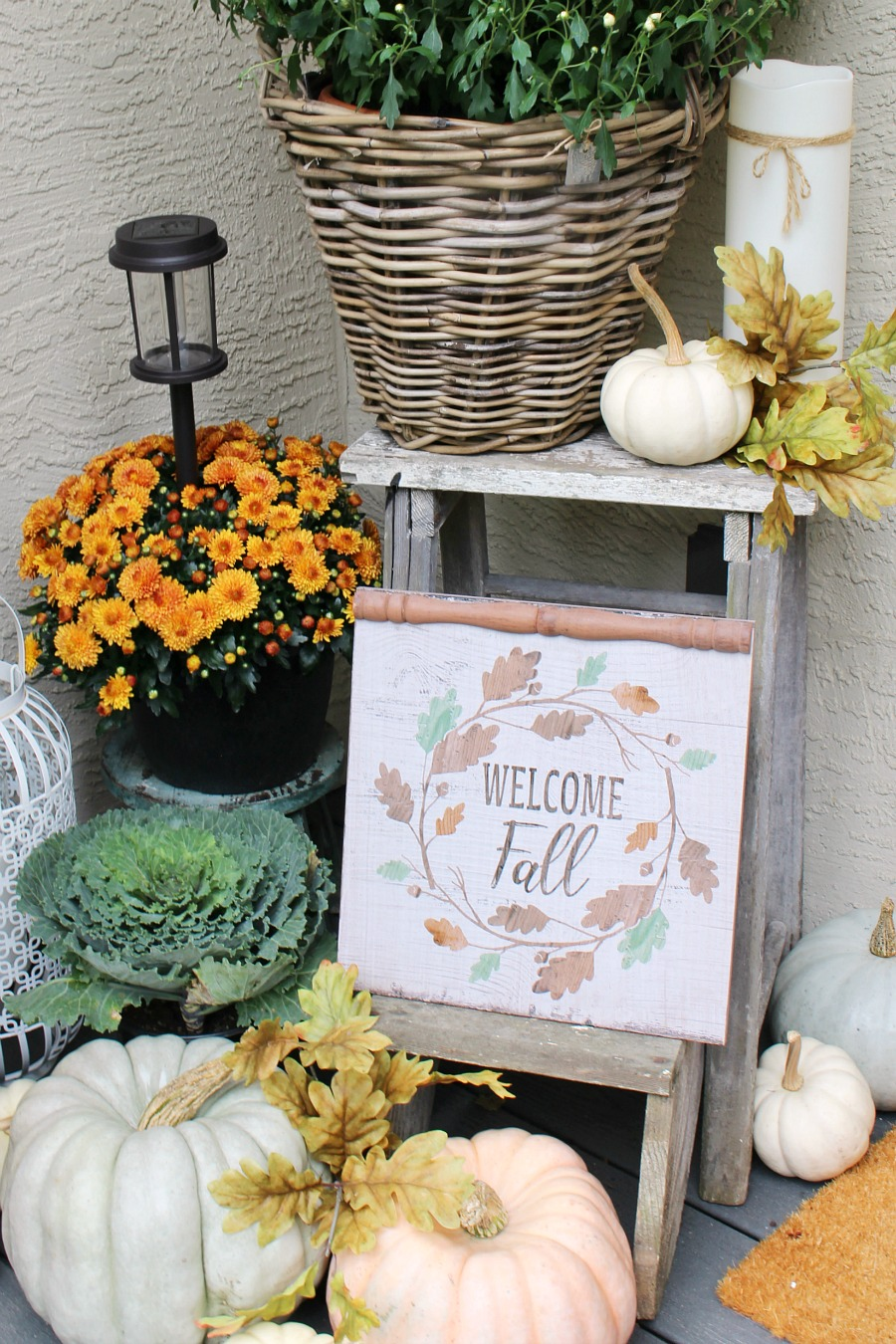 Rustic step ladder with pumpkins and a fall sign on a fall front porch.