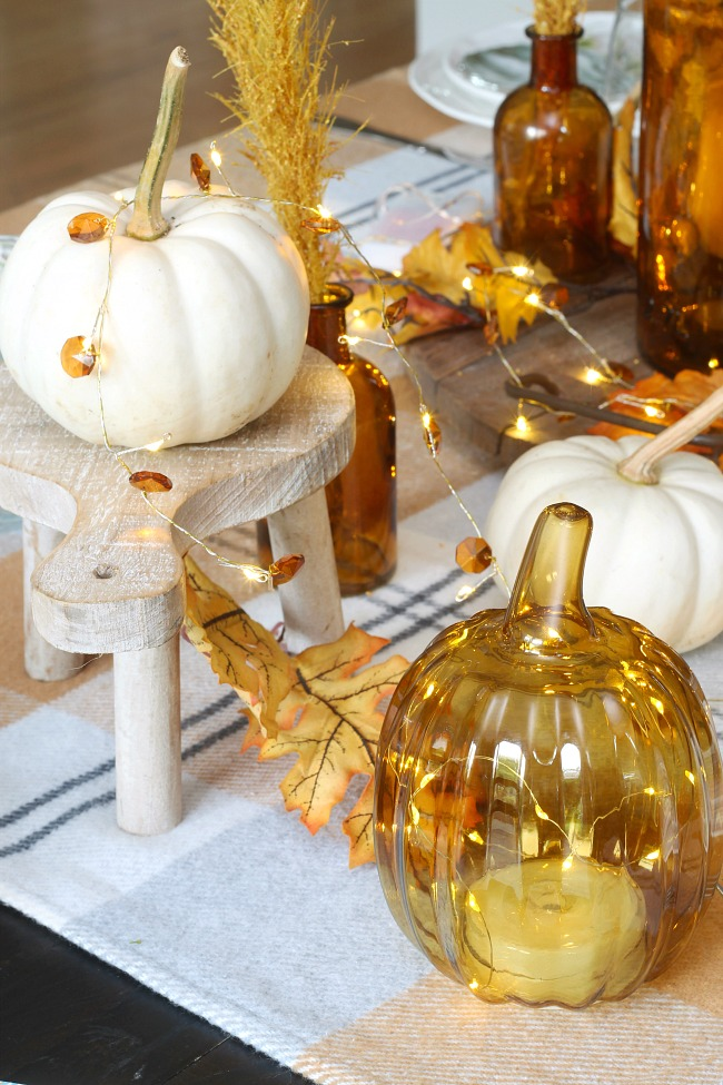 Fall tablescape with glowing lights, amber glass, and white pumpkins on a wood stand.