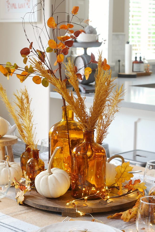 Pretty fall tablescape centerpiece using amber bottles, white pumpkins and golden fall leaves.