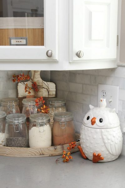 Fall kitchen corner with owl cookie jar and mason jars filled with dry goods.