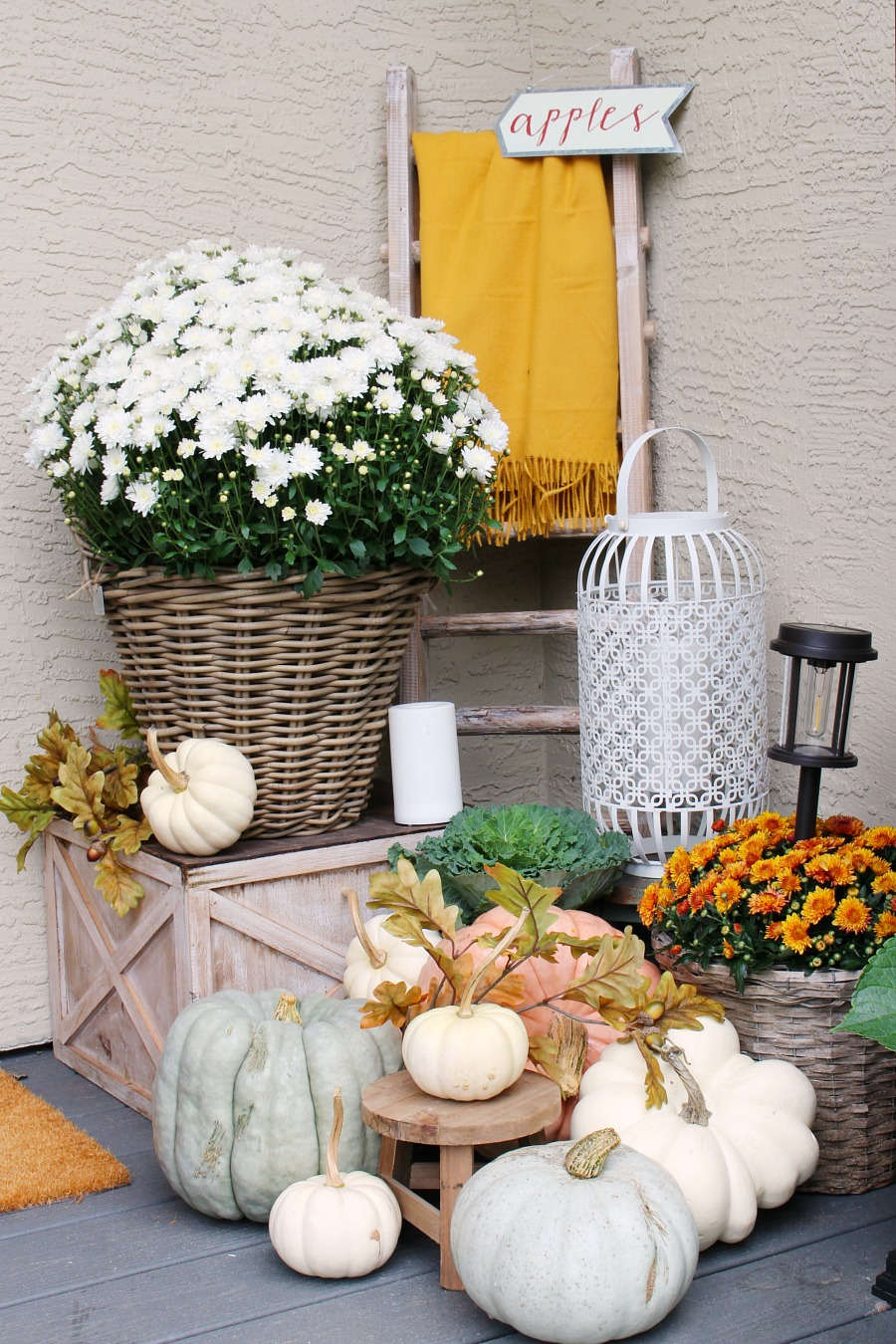 Fall front porch with a blanket ladder, mums and pumpkins.