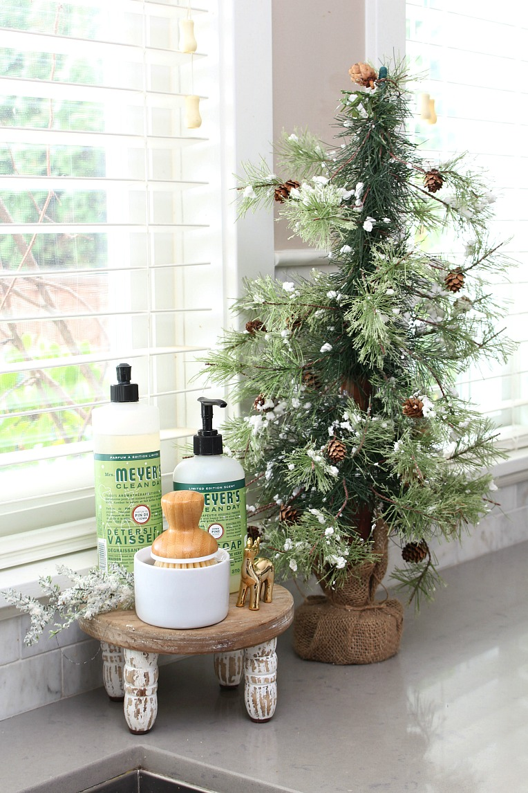 Christmas dish soap and a Christmas tree by the kitchen sink.