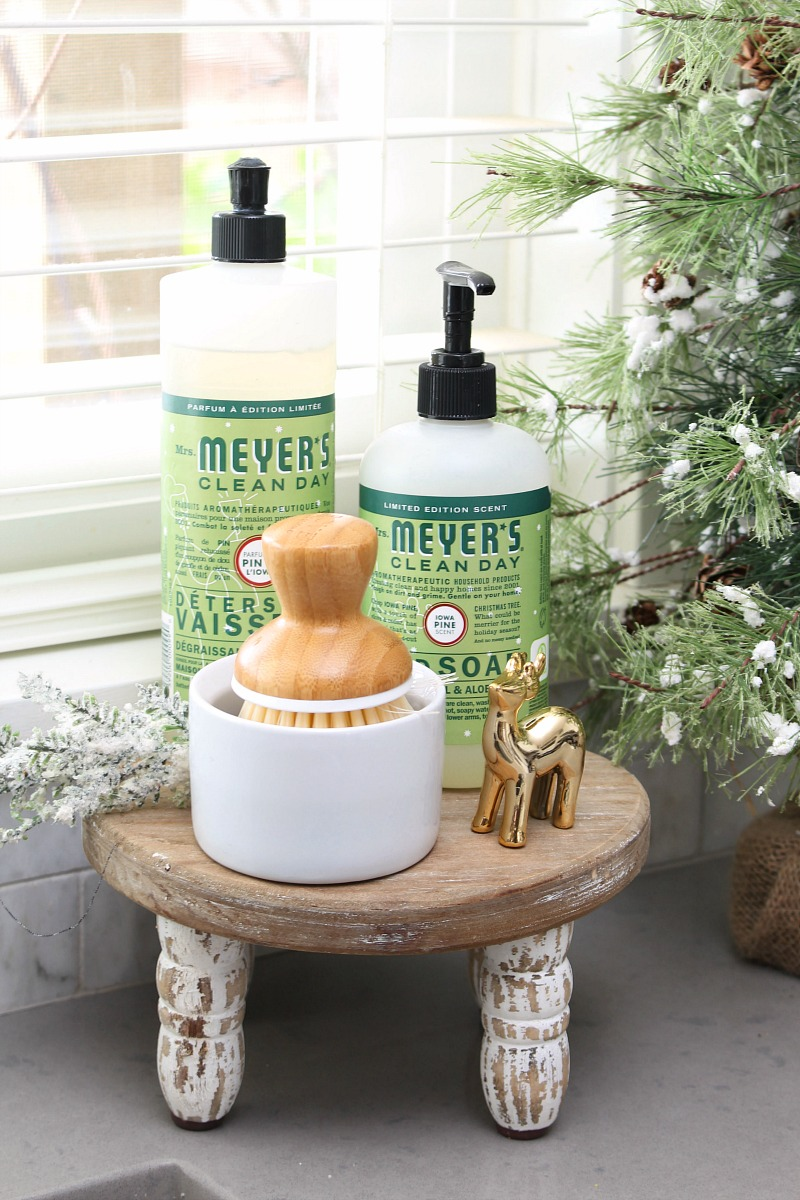 Christmas dish soaps and a little gold reindeer on a wood stand.