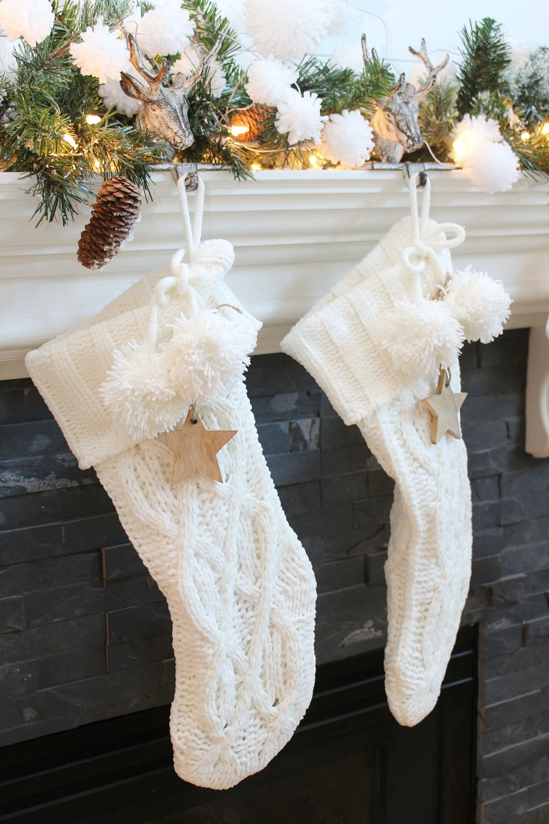 Neutral Christmas mantel decor with white knit stockings.