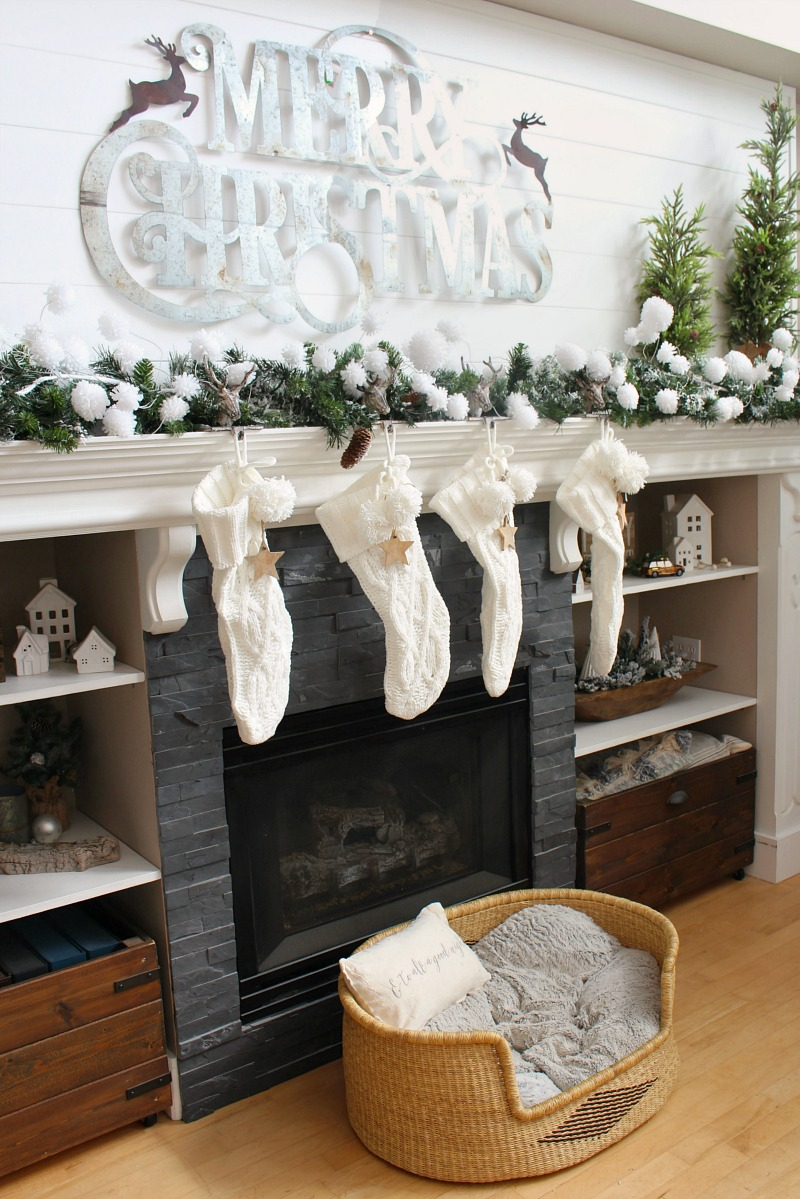 Neutral Christmas mantel decor with large metal Merry Christmas sign.