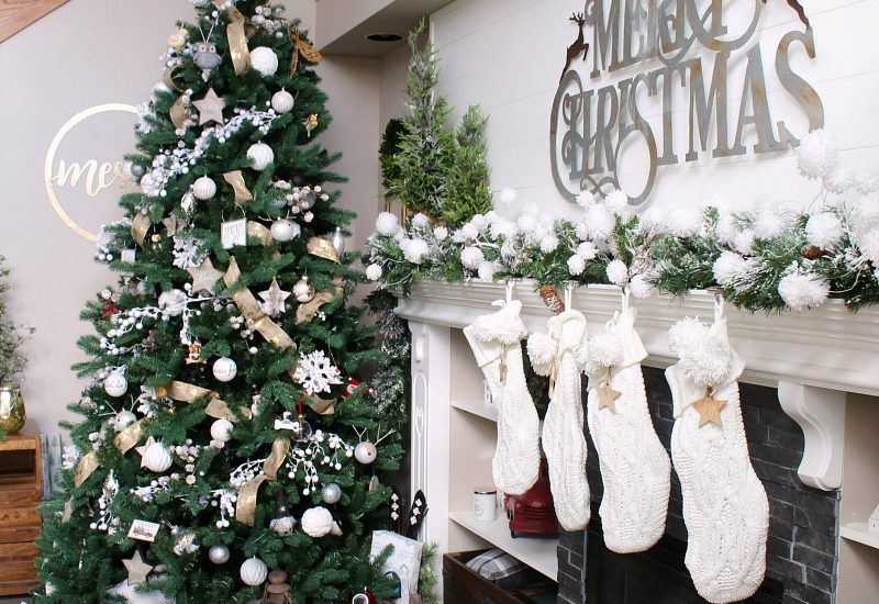 Christmas mantel decorated with faux greenery, whites and metallics.