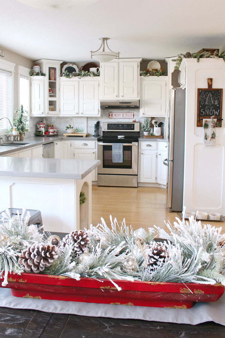 White kitchen decorated for Christmas with greens.