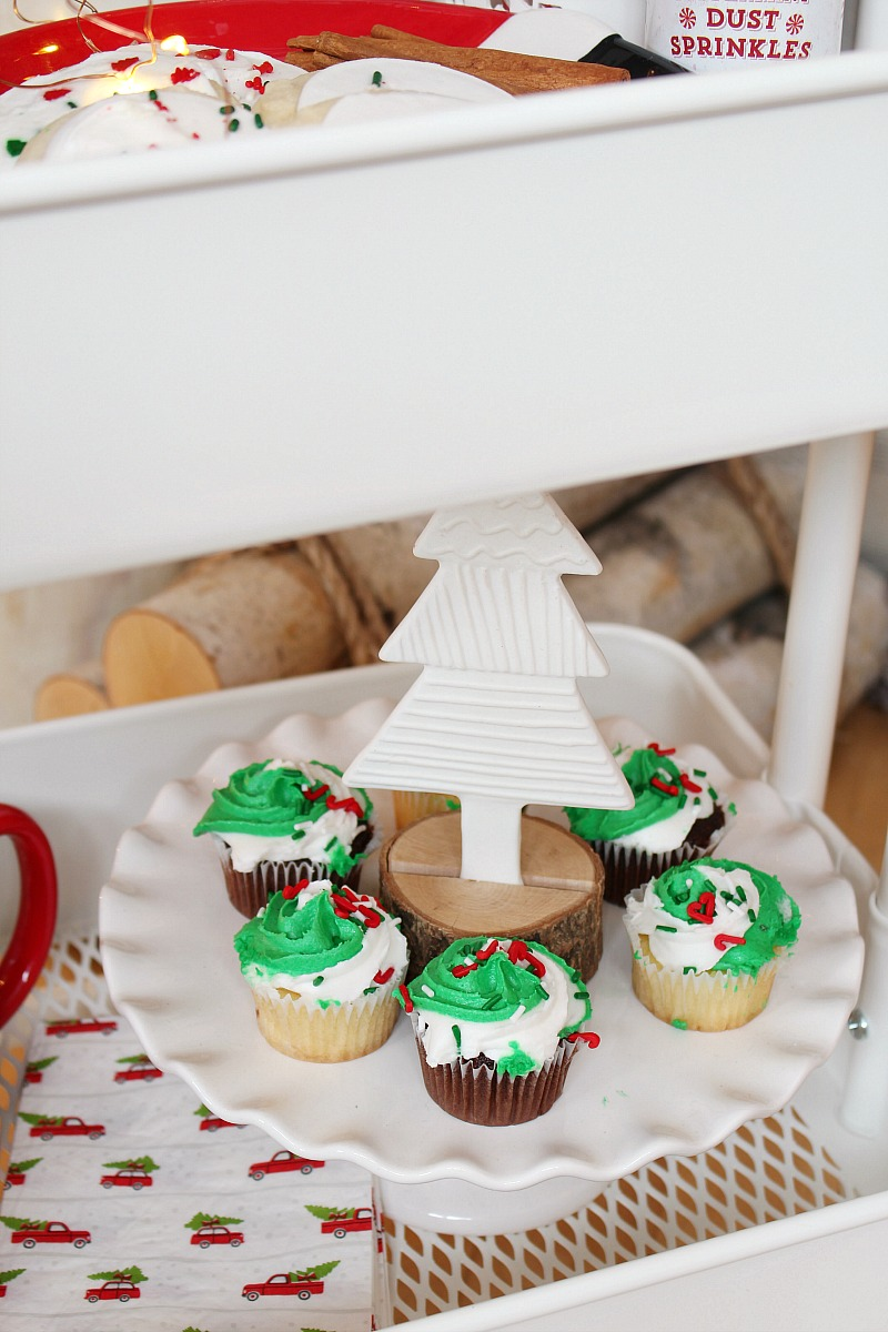 Rolling cart filled with Christmas treats including a cake stand with cupcakes