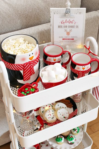 Christmas movie night cart with popcorn, hot chocolate and Christmas treats.