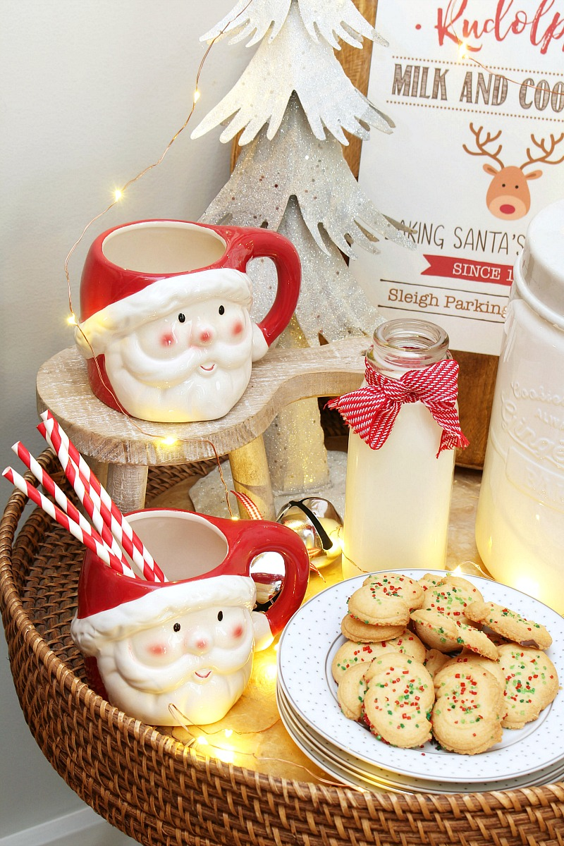 Milk and cookie bar with Santa mugs and Christmas cookies.