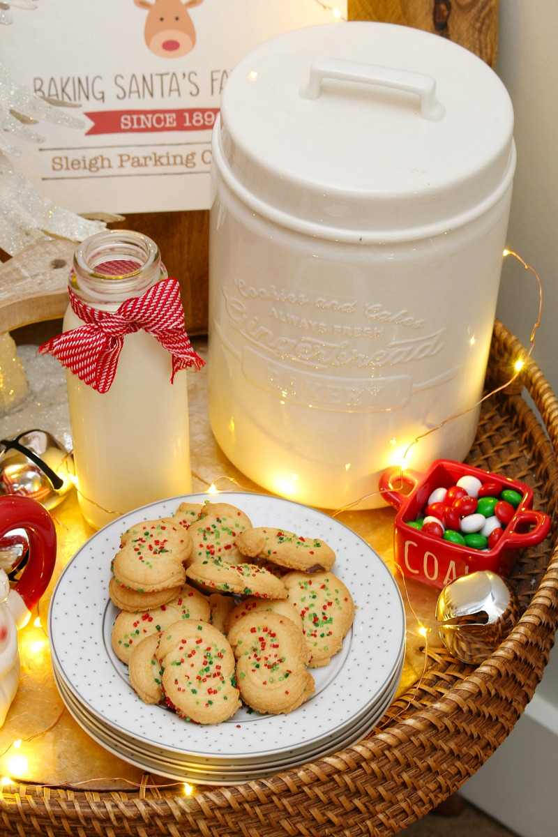 Adorable Christmas milk and cookie bar with white cookie jar and a plate full of Christmas cookies.