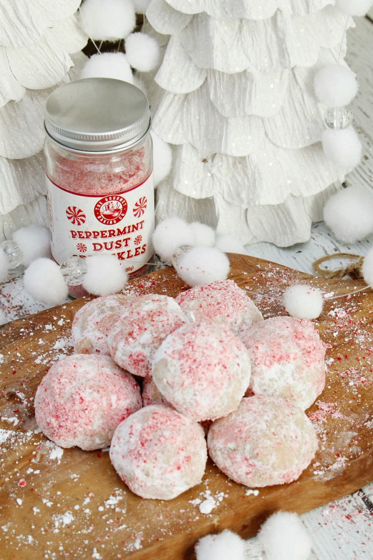 Peppermint snowball cookies on a wood cutting board.