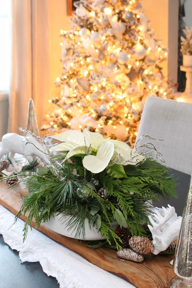 Poinsettia DIY Christmas centerpiece on a Christmas table with Christmas tree.