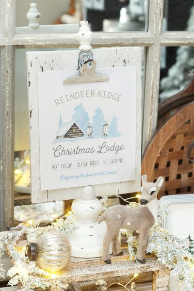 Reindeer Ridge Christmas Lodge free printable on a white clipboard frame with reindeer and twinkle lights.