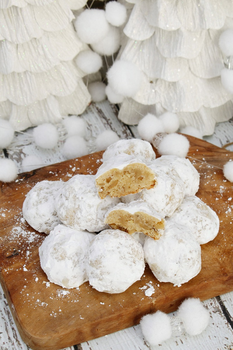 Pecan snowball cookies on a wood tray.