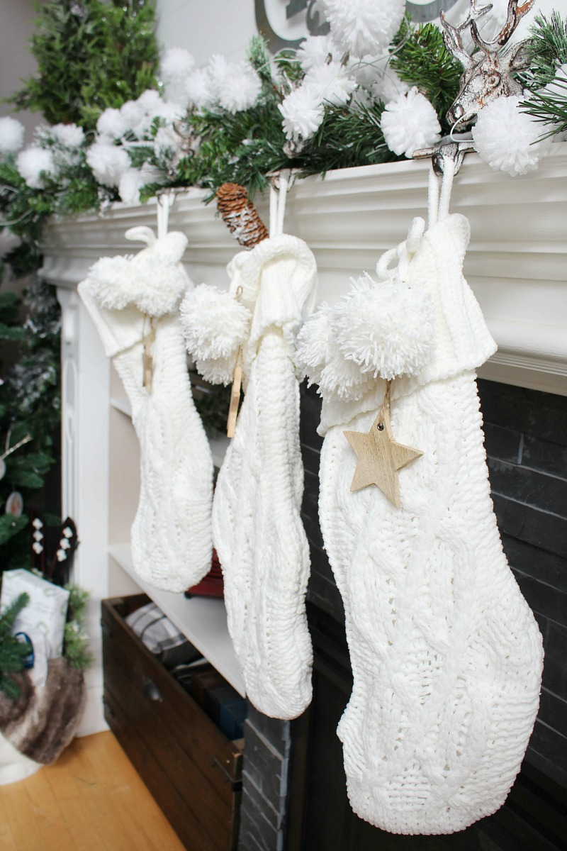 White knit stockings on a Christmas mantel with wood star tags.