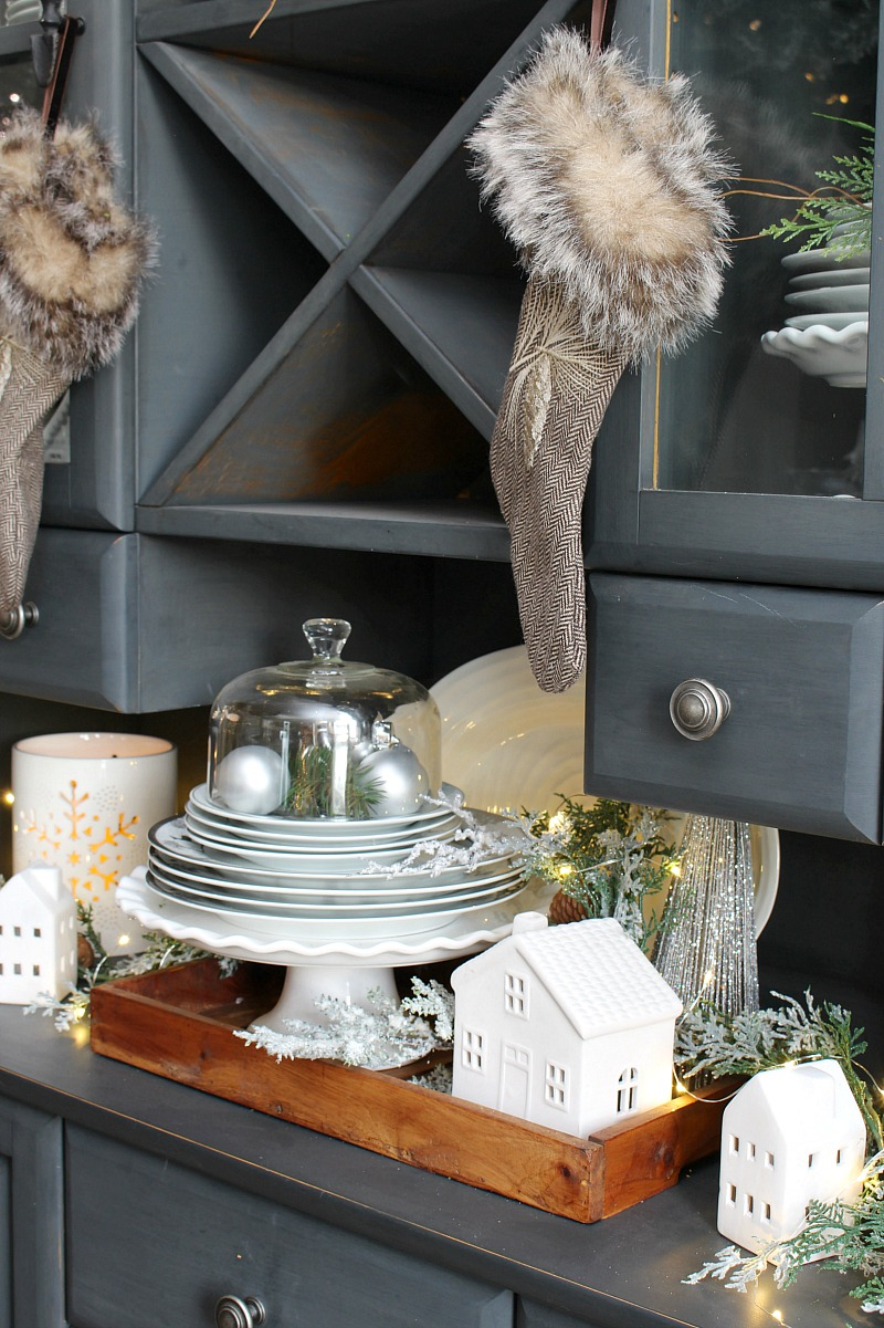 Christmas vignette with white ceramic houses on a black buffet and hutch.