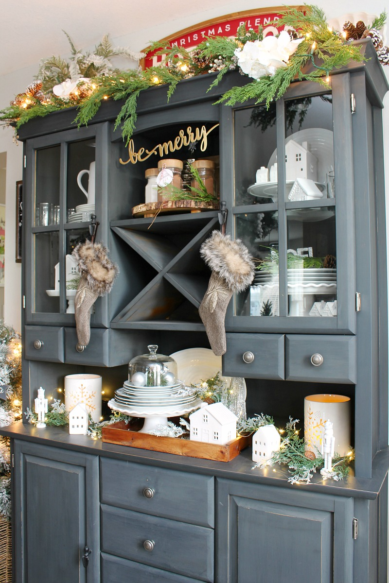 Beautiful black buffet and hutch decorated for Christmas with white and greenery.