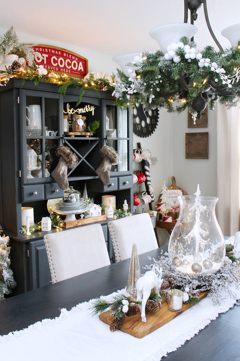 Black and white farmhouse style dining room decorated for Christmas using neutrals and a few pops of red.