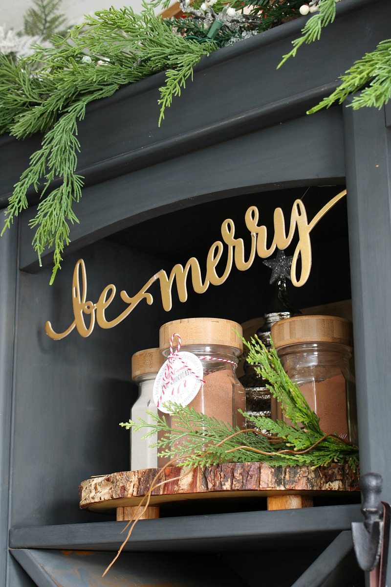 Mason jars filled with hot chocolate powder and free printable hot chocolate bar labels with Be Merry banner.
