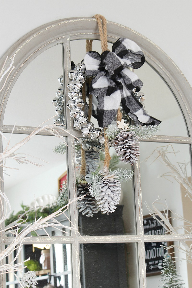 Large mirror decorateed with a jingle bell wreath for Christmas.