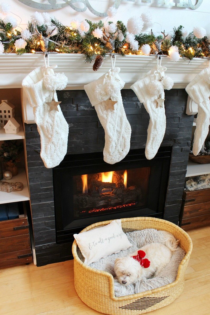 Woven dog bed in front of a Christmas fireplace.