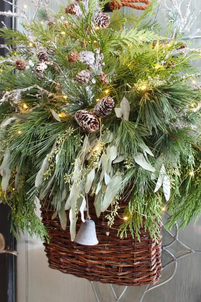 Christmas basket wreath with fresh greenery and fairy lights.