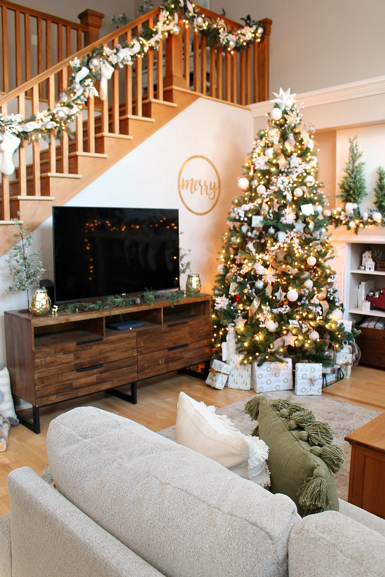 Cozy family room decorated for Christmas with green, white, and metallics.