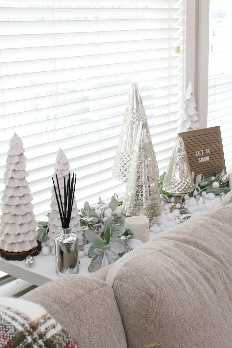 White and mercury glass Christmas tree vignette on a sofa table.