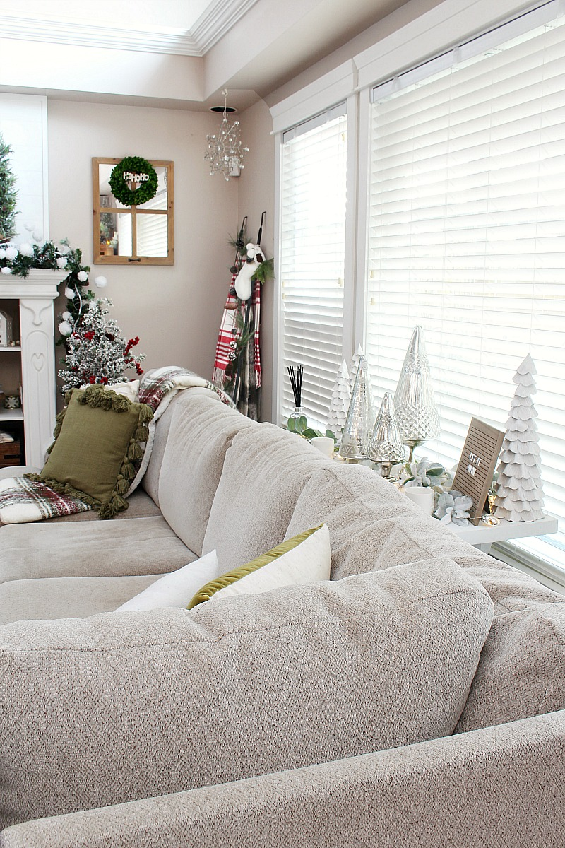 Neutral colored sectional in a family room decorated for Christmas.
