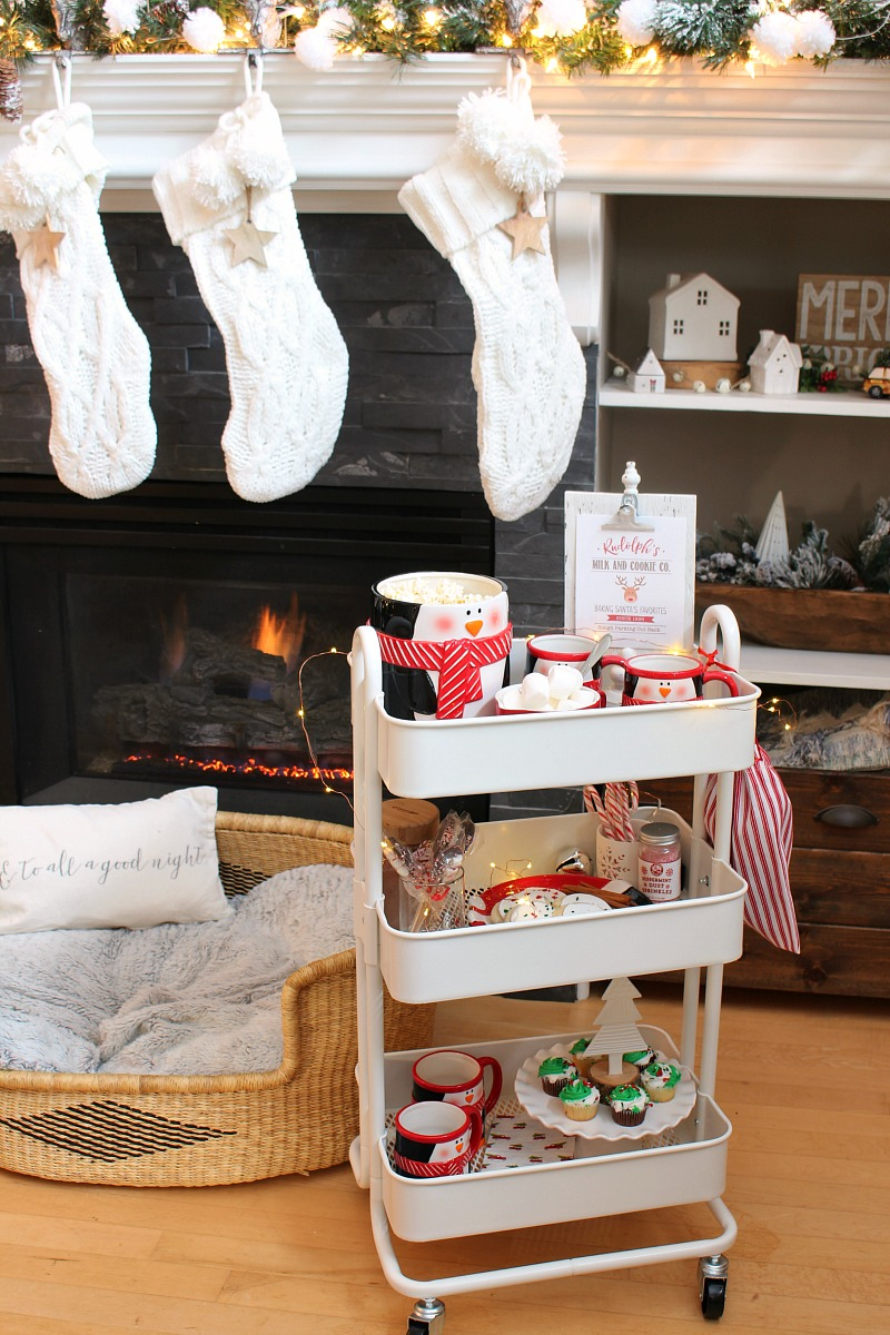 Christmas movie night cart with Chrismas treats in front of a Christmas mantel.
