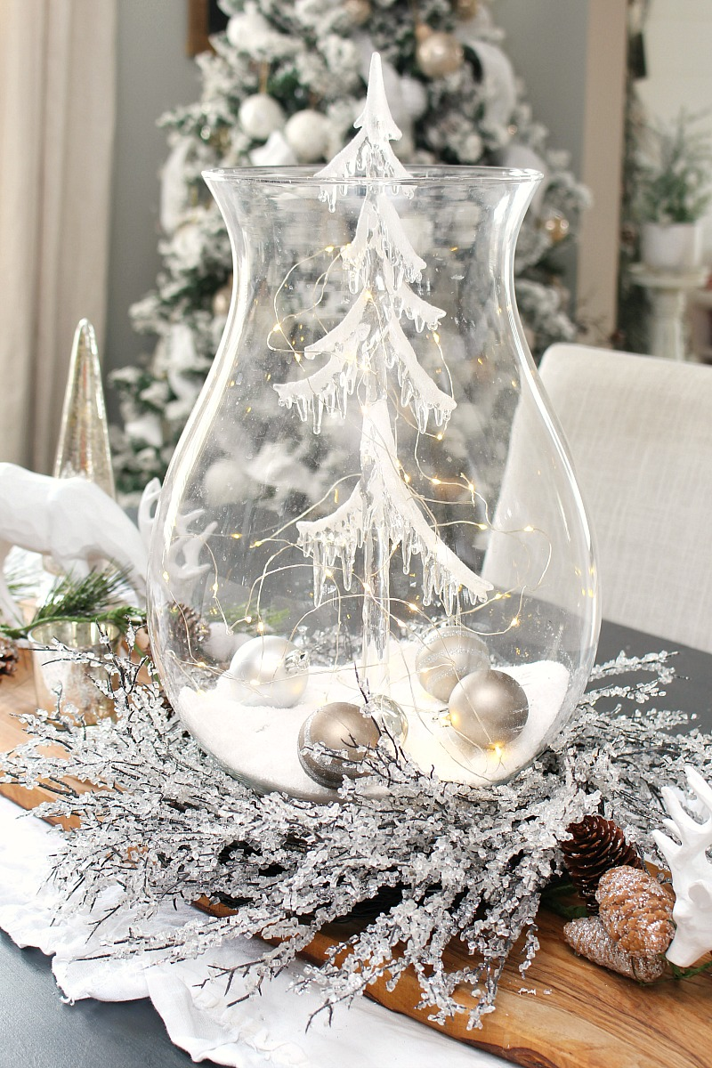 Christmas centerpiece using a large glass candle holder, glass Christmas tree and lights.