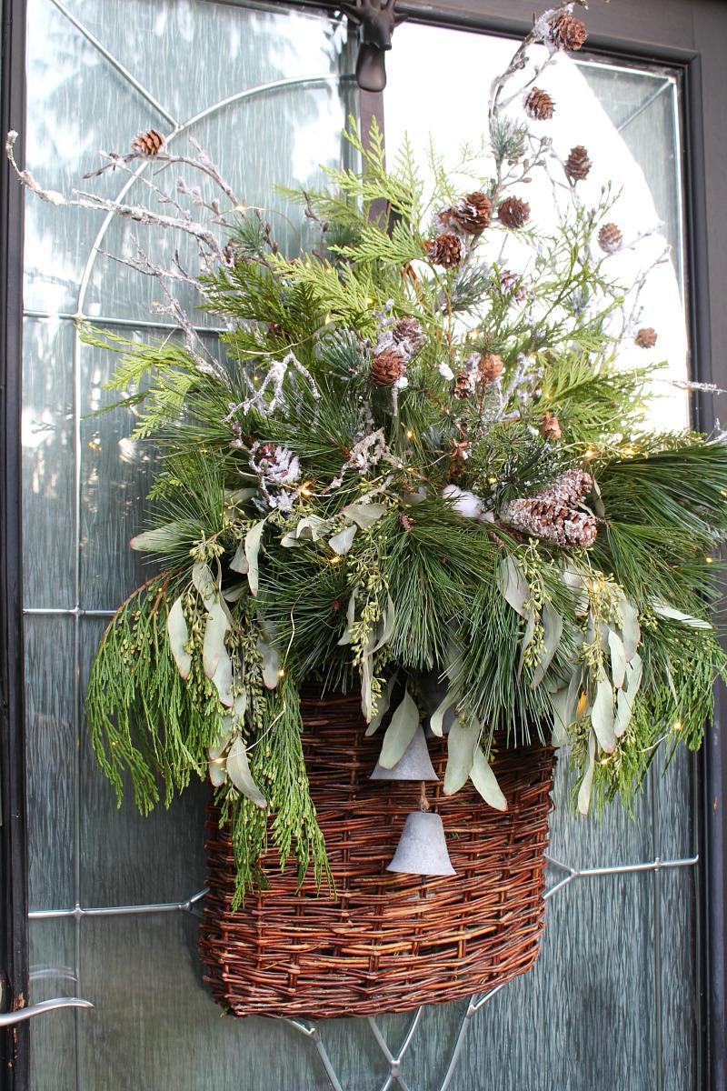 Christmas basket wreath with fresh greenery and fairy lights.