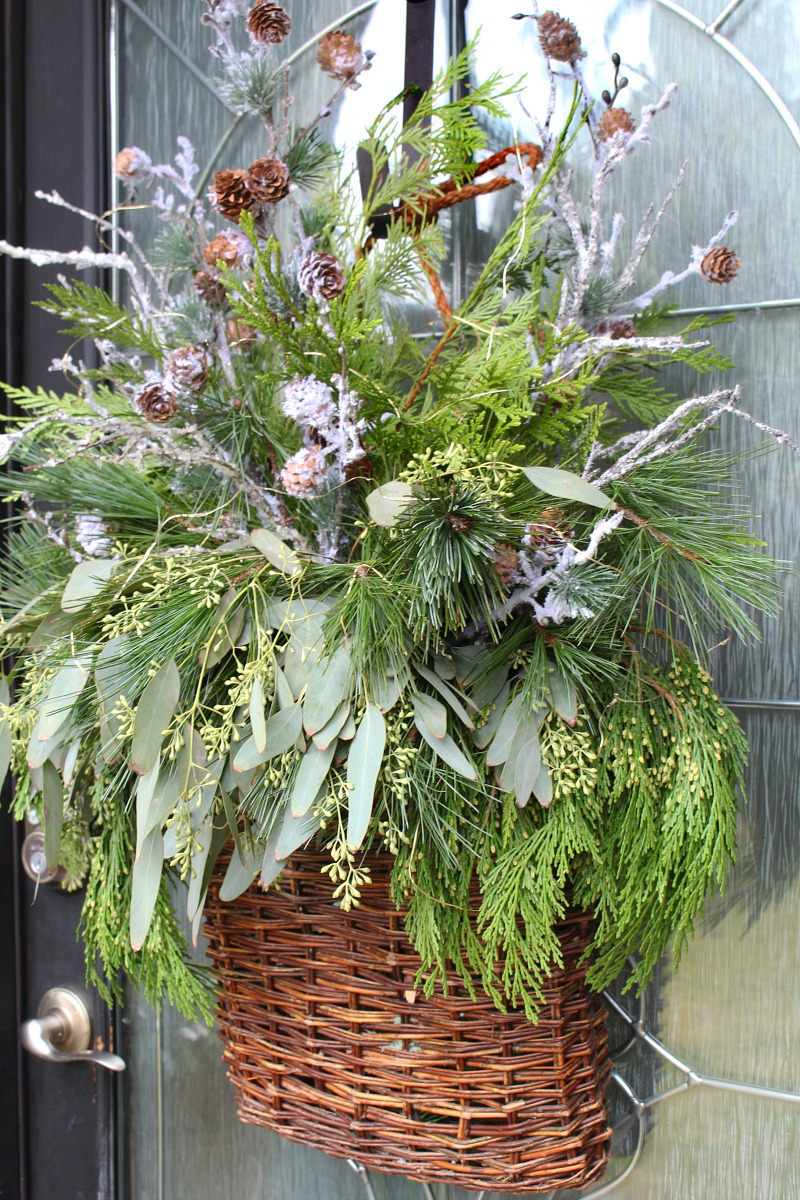 Beautiful Christmas basket wreath with fresh greenery and snowy branches.