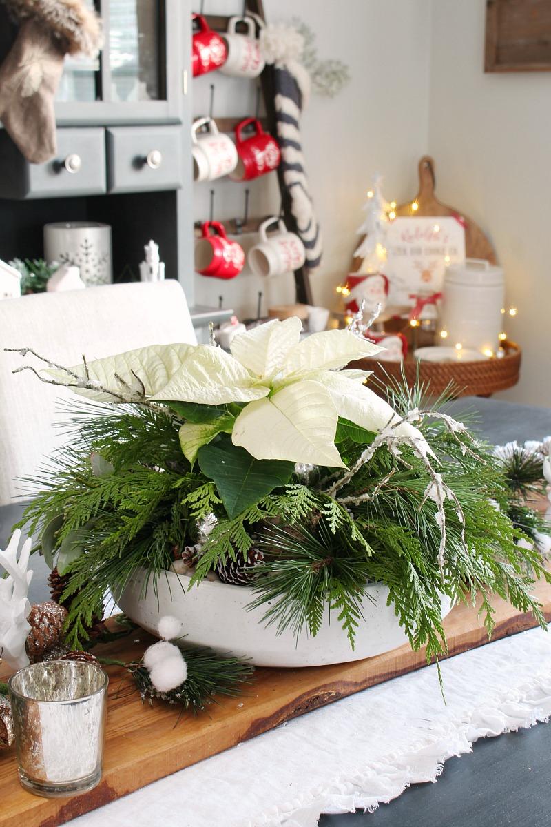 Simple DIY Christmas centerpiece idea with a poinsettia and fresh greenery.