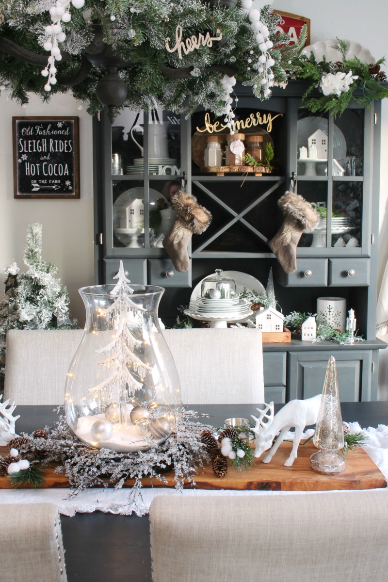 Black and white farmhouse style dining room decorated for Christmas with silver and neutral tones.