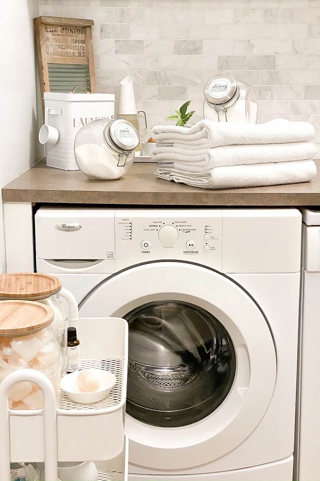 Organized laundry room with laundry cart and glass canisters.