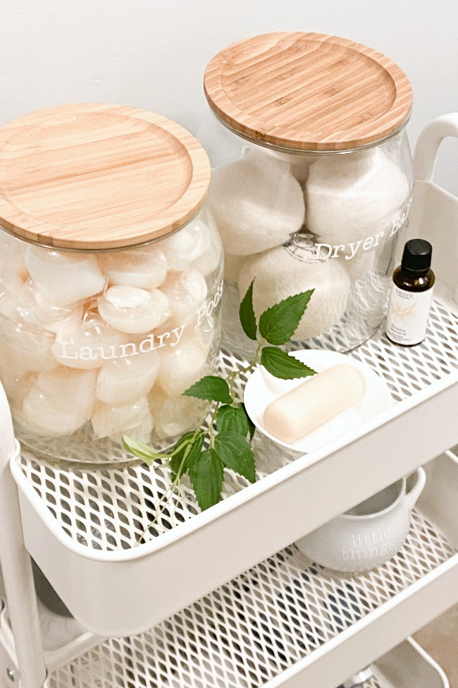 Glass laundry storage jars with vinyl word labels on a cart.