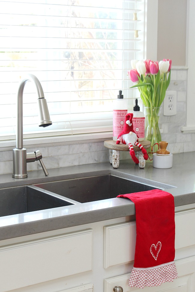White farmhouse kitchen decorated for Valentine's Day.