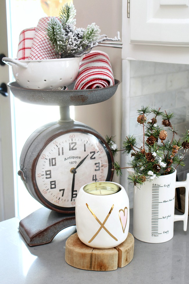 Red tea towels added to a kitchen clock scale for easy Valentine's Day decor.