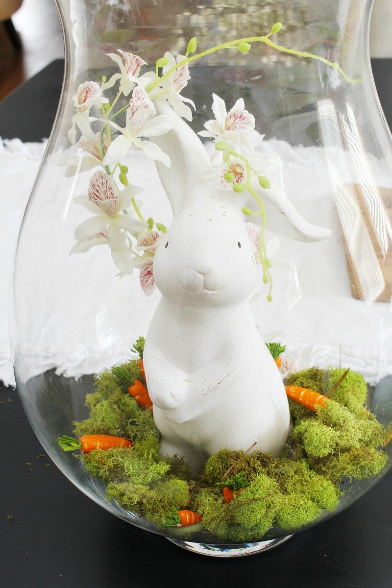 Glass hurricane vase with white ceramic bunny for Easter centerpiece.