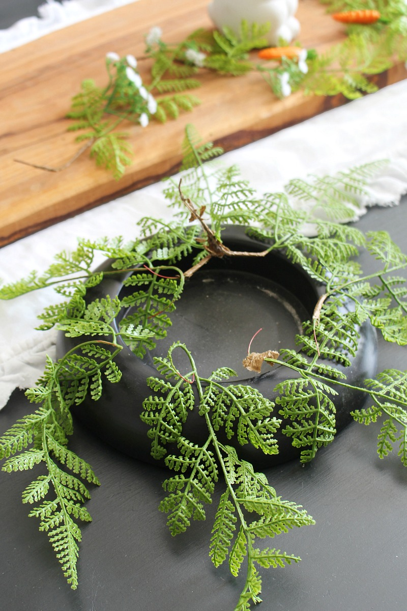 Fern leaves around a hurricane vase base for an Easter centerpiece.
