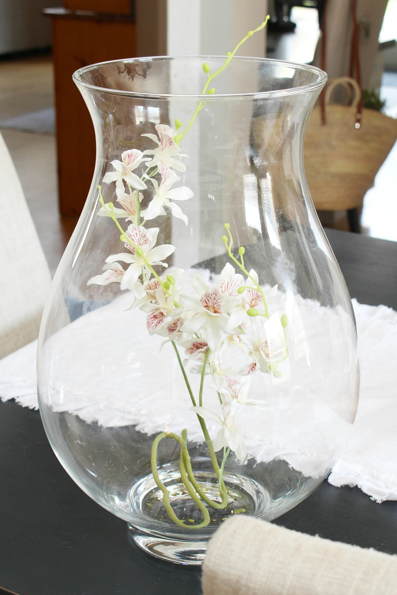 Glass hurricane vase with faux flowers for Easter centerpiece.