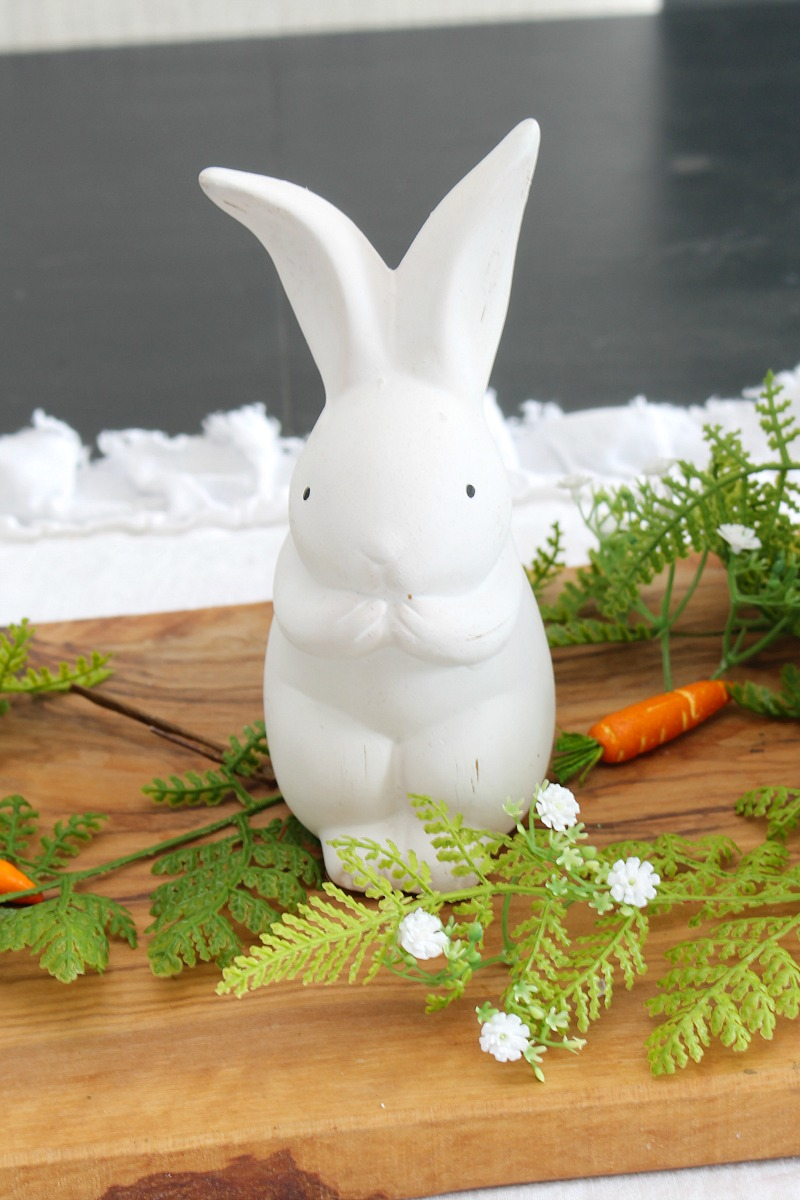 Easter bunny centerpiece with white ceramic bunnies and greenery.