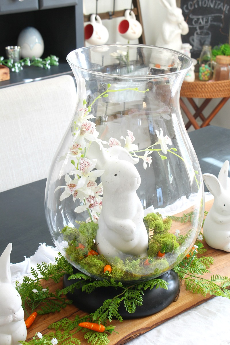 Cute Easter centerpiece with glass hurricane vase and ceramic bunnies.