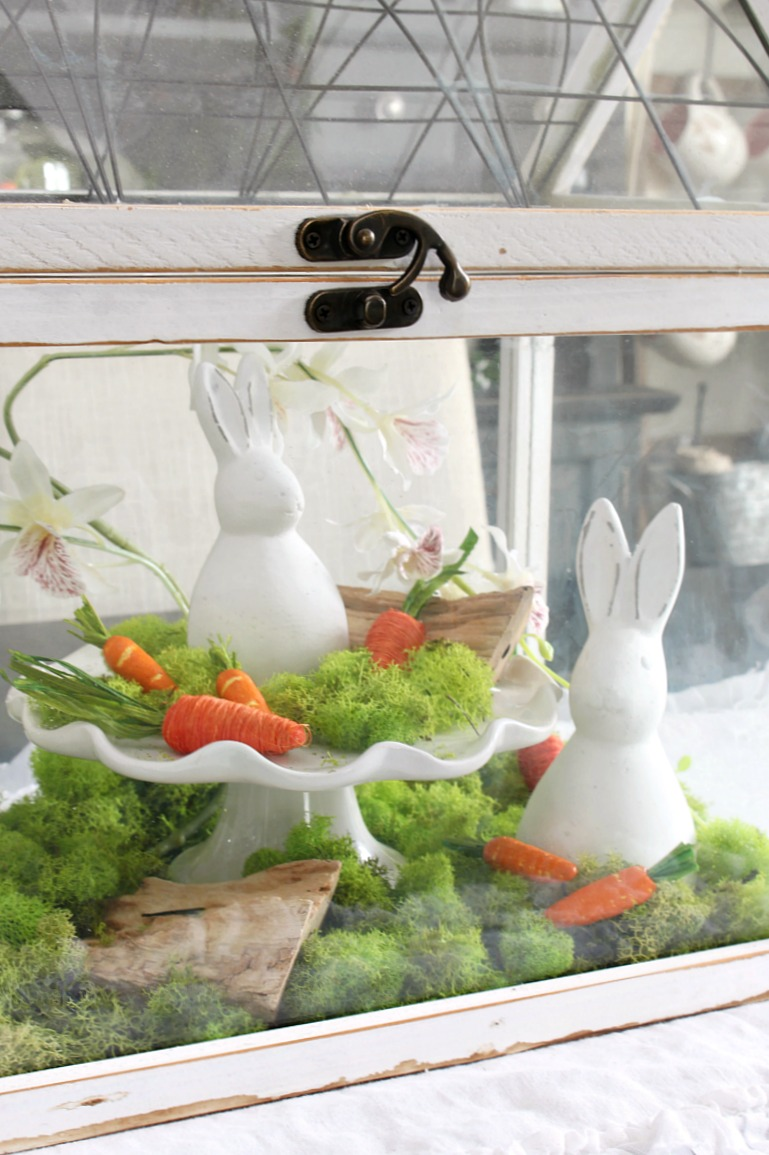 Easter terrarium with moss and ceramic bunnies.