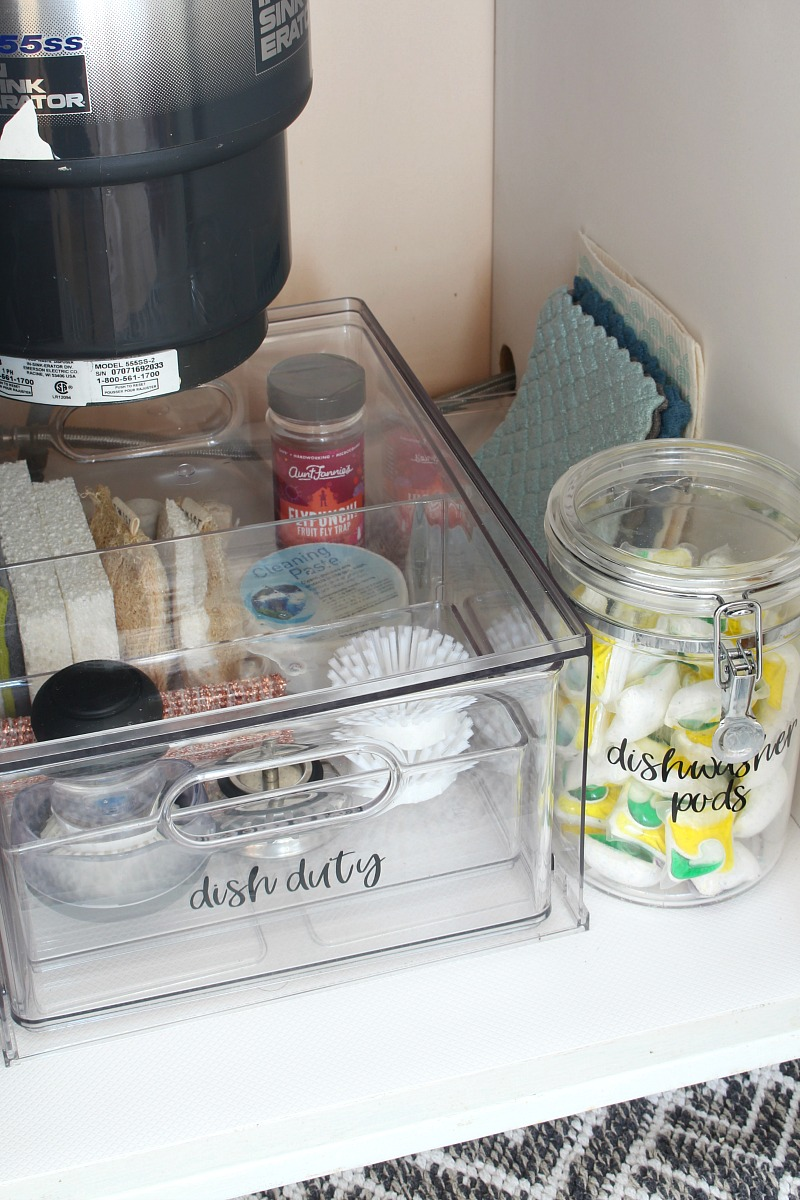 Acrylic drawer organizer used to organize kitchen cleaning products under the kitchen sink.