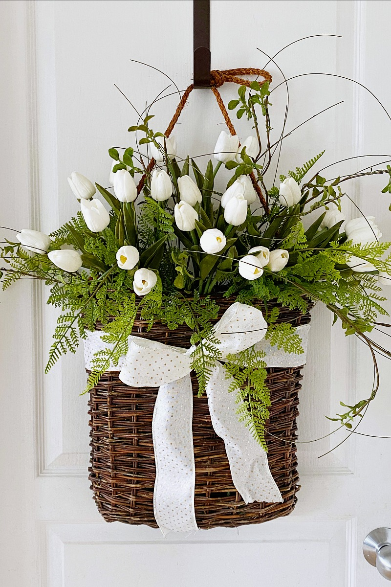 Pretty spring basket tulip wreath on a white door.