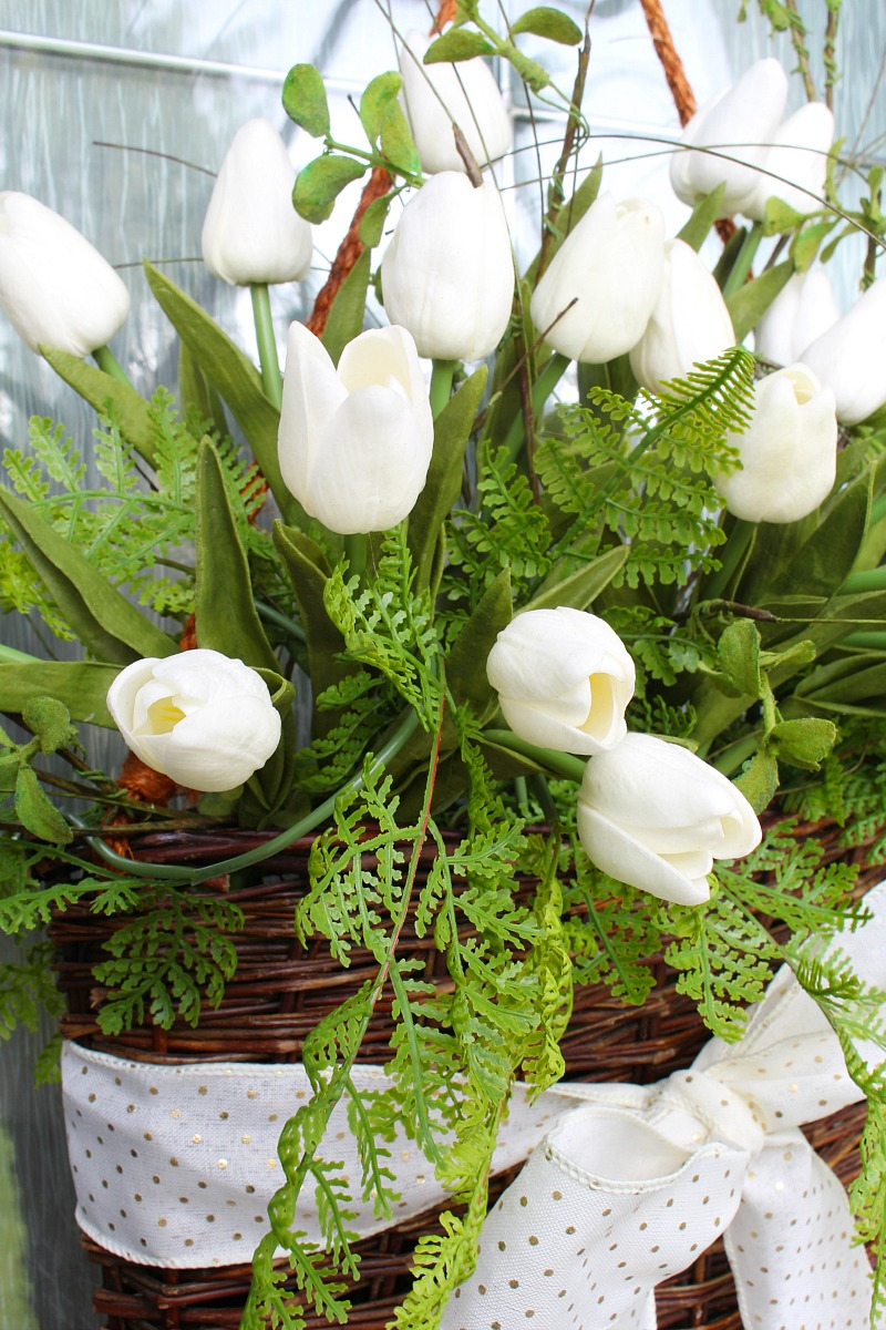White tulips and greenery in a willow basket.
