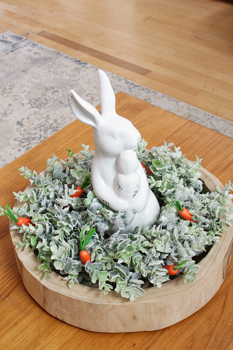 Easter centerpiece with wood tray, greenery and white ceramic rabbit.